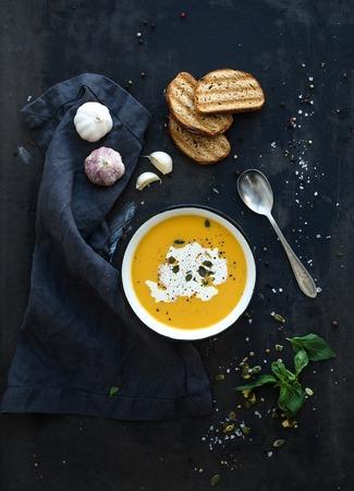 그런 지 검은 배경에 소박한 금속 접시에 크림, 씨앗, 빵과 신선한 바질과 호박 수프. 평면도 스톡 콘텐츠