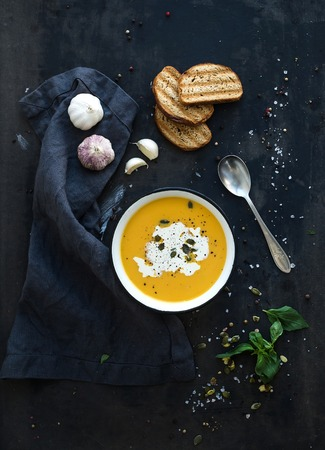 meal preparation: Pumpkin soup with cream, seeds, bread and fresh basil in rustic metal plate on grunge black background. Top view Stock Photo