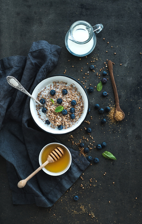 Rustic healthy breakfast set. Cooked buckwheat groats with milk, blueberries and honey on dark grunge backdrop. Top view