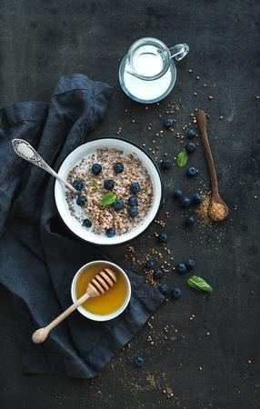 Rustieke gezond ontbijt set. Gekookt boekweitgrutten met melk, bosbessen en honing op een donkere grunge achtergrond. Bovenaanzicht