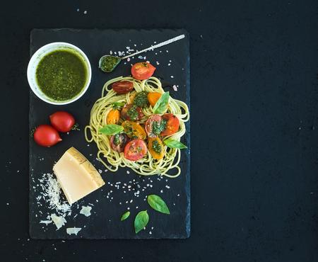 amarillo y negro: Espaguetis con salsa de pesto, tomates cherry asados-, albahaca fresca y queso parmesano en la placa de piedra negro atiende a más de telón de fondo oscuro del grunge. Vista superior, espacio de la copia Foto de archivo