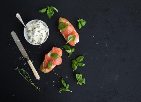 bocadillo: Salmon, ricotta y albahaca sándwiches con baguette sobre el fondo negro del grunge. Vista superior, espacio de la copia