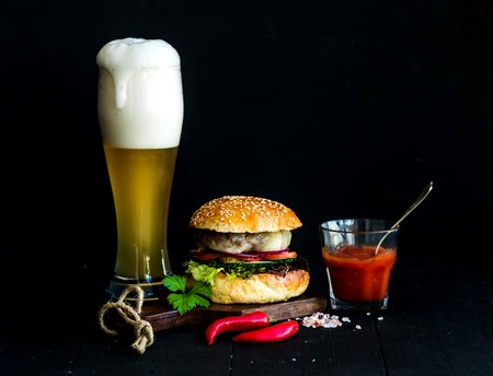 black background: Fresh homemade burger on wooden serving board with spicy tomato sauce, sea salt, herbs and glass of light beer over black  background Stock Photo