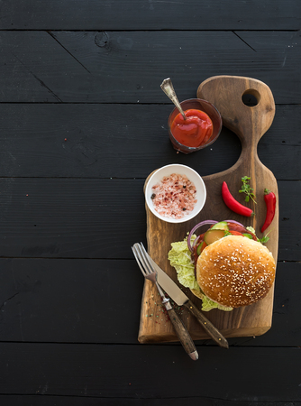 Fresh homemade burger on dark serving board with spicy tomato sauce, sea salt over dark wooden background. Top view, copy space