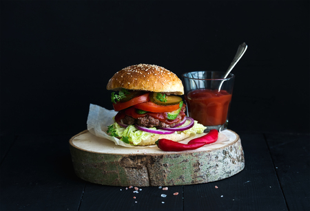 Fresh homemade burger on wooden serving board with spicy tomato sauce, sea salt and herbs over black  background Stok Fotoğraf