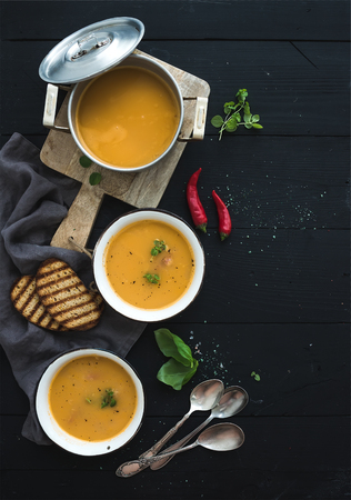Red lentil soup with spices, herbs, bread in a rustic metal saucepan and bowls, over dark wood backdrop, top view, vertical, copy space