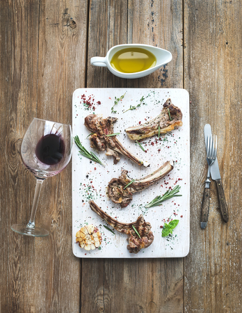 rack of lamb: Grilled lamb chops. Rack of Lamb with garlic, rosemary and spices on white serving board, wine glass, oil in a saucer, dinnerware over rustic wood background. Top view Stock Photo