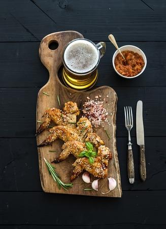 alitas de pollo: Alas de pollo fritas a bordo porci�n r�stico, salsa picante de tomate, las hierbas y la taza de cerveza ligera sobre el negro tel�n de fondo de madera, vista desde arriba