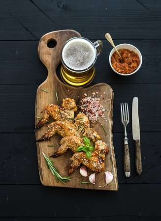 bar top: Fried chicken wings on rustic serving board, spicy tomato sauce, herbs and mug of light beer over black wooden backdrop, top view