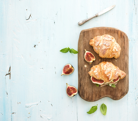Freshly baked croissants with fresh figs and prosciutto on serving board over blue rustic wooden backdrop, top view, copy space Stock Photo