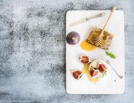 Camembert of brie kaas met verse vijgen, honingraat en glas witte wijn op een witte portie bord over grunge rustieke grijze achtergrond, bovenaanzicht, kopieer ruimte Stockfoto