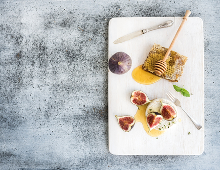 cheese plate: Camembert or brie cheese with fresh figs, honeycomb and glass of white wine on white serving board over grunge rustic grey backdrop, top view, copy space Stock Photo