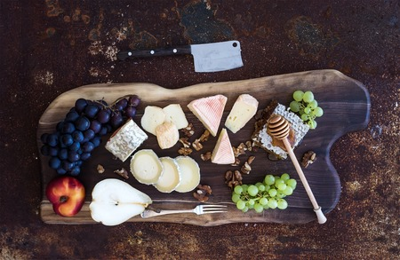 Wine appetizers set: French cheese selection, honeycomb, grapes, peach and walnuts on rustic wooden board over dark grunge metal background. Top view, Stock Photo