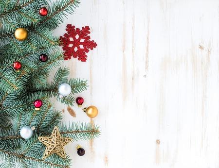 Kerstmis of Nieuwjaar decoratie achtergrond: bont-boom takken, kleurrijke glazen bollen en glinsterende sterren op een witte houten achtergrond, bovenaanzicht, kopieer ruimte Stockfoto