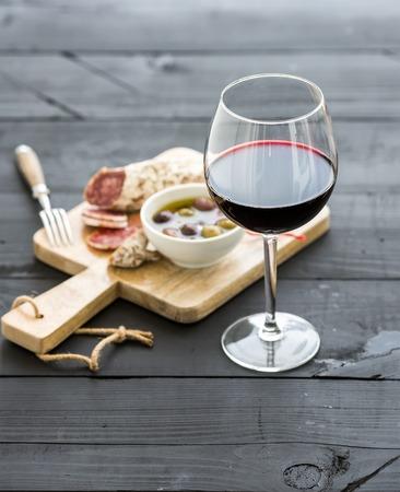 와인 전채 설정합니다. 레드 와인의 유리, 프랑스어 소시지와 검은 나무 배경에 올리브, 선택적 포커스