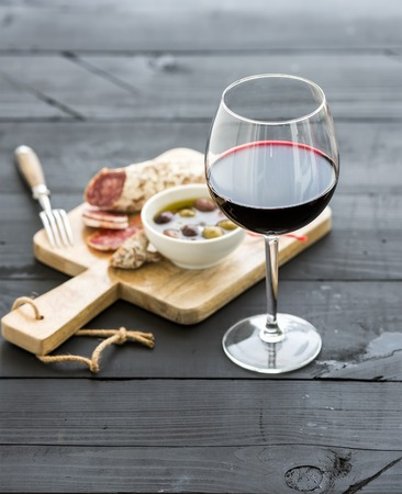 Wine appetizer set. Glass of red wine, French sausage and olives on black wooden backdrop, selective focus Stockfoto