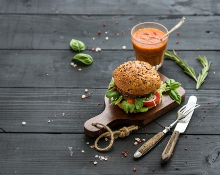 Fresh homemade burger on dark serving board with spicy tomato sauce, sea salt and herbs over dark wooden background, copy space Stockfoto