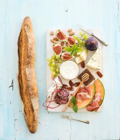 pan frances: El vino y el conjunto de aperitivos. Baguette, los higos, las uvas, las nueces, las variedades de quesos, aperitivos a base de carne, hierbas sobre fondo azul claro, vista desde arriba