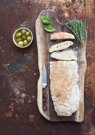 Freshly baked homemade ciabatta bread with olives, basil and thyme on walnut wood board over grunge rusty metal background, top view copy space