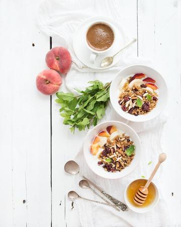 yogur: Desayuno saludable. Tazón de granola de avena con yogurt, fruta fresca, menta y miel. Taza de café, cubiertos de la vendimia. Vista superior, espacio de la copia