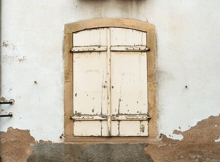 historic and vintage: French window with closed old medieval wooden shutters