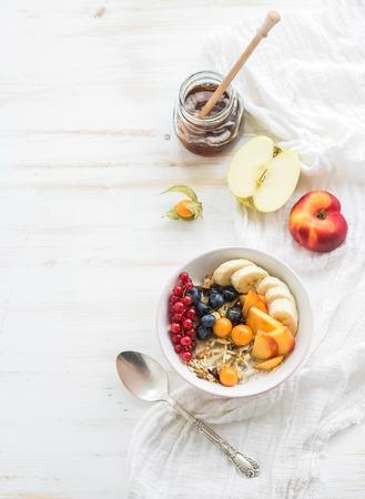 건강 한 아침 식사. 요구르트, 신선한 딸기, 과일과 꿀 귀리 놀라의 그릇입니다. 상위 뷰, 복사 공간