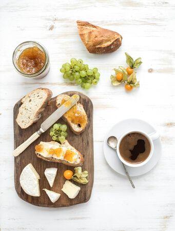 breakfast: Conjunto del desayuno. Queso Brie y sándwiches de mermelada de higos con uvas frescas, cerezas de tierra. Taza de café. Vista superior, espacio de la copia