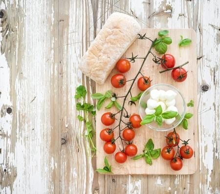 colazione: Pane ciabatta con banch di pomodorini, basilico e mozzarella su rustico tavola di legno su vecchio fondale bianco, vista dall'alto Archivio Fotografico