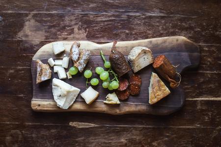 pan y vino: aperitivos sistema del vino: la carne y el queso de la selección, las uvas y pan sobre una tabla de madera rústica sobre un fondo de madera oscura. Vista superior