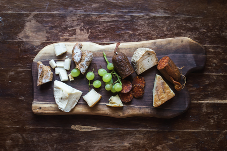 cheese platter: Wine appetizers set: meat and cheese selection, grapes and bread on a rustic wooden board over a dark wood background. Top view