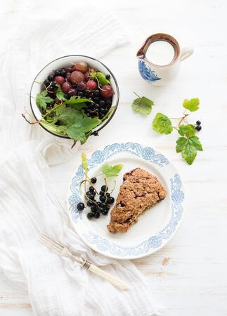 bisquit: Black-currant scone bisquit with bowl of fresh garden berries and cream, top view