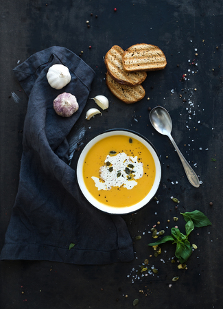 Pumpkin soup with cream, seeds, bread and fresh basil in rustic metal plate on grunge black background. Top view Stock Photo