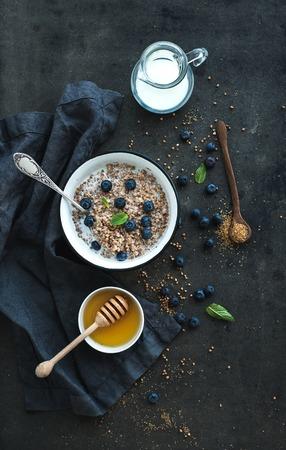 kasha: Rustic healthy breakfast set. Cooked buckwheat groats with milk, blueberries and honey on dark grunge backdrop. Top view