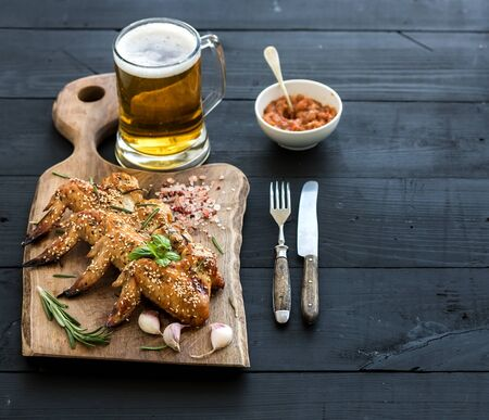 bar top: Fried chicken wings on rustic serving board, spicy tomato sauce, herbs and mug of light beer over black wooden backdrop, copy space, selective focus