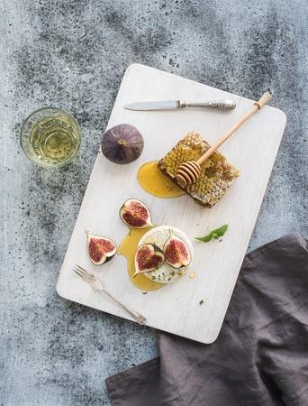 peine: Camembert o brie queso con higos frescos, panales de miel y un vaso de vino blanco a bordo de servir de blanco sobre el grunge contexto gris rústica, vista desde arriba