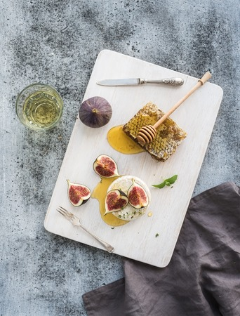 Camembert or brie cheese with fresh figs, honeycomb and glass of white wine on white serving board over grunge rustic grey backdrop, top view