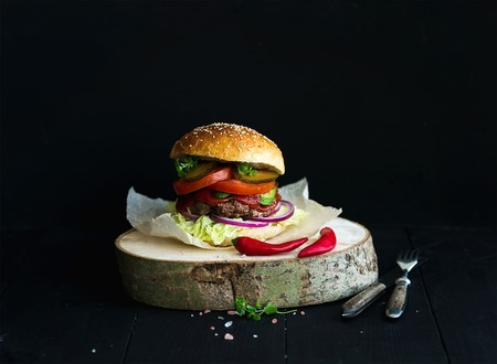 beef burger: Fresh homemade burger on wooden serving board with spicy tomato sauce, sea salt and herbs over black  background Stock Photo