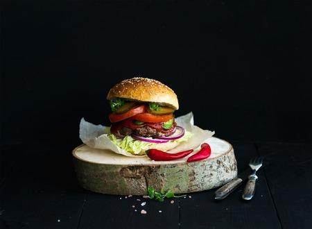 hamburguesa: Hamburguesa casera fresco a bordo de la porci�n de madera con salsa picante de tomate, sal marina y hierbas sobre el fondo negro