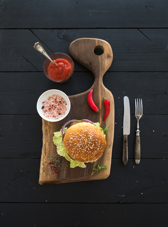 classic burger: Fresh homemade burger on dark serving board with spicy tomato sauce, sea salt over dark wooden background. Top view, copy space