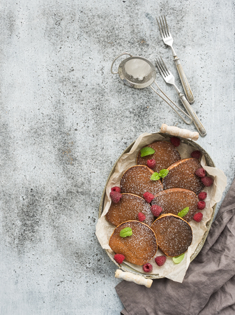 grunge silverware: Breakfast set. Homemade buckwheat pancakes with fresh raspberry in  serving tray, kitchen napkin, vintage silverware on grey grunge background. Top view, cpy space