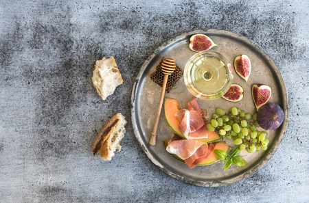 honeycomb: Wine appetizer set. Glass of white wine, honeycomb with drizzlier, figs, melon with prosciutto and grapes on silver tray over rustic grunge surface. Top view, copy space Stock Photo
