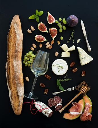 merienda: El vino y el conjunto de aperitivos. Baguette, vaso de blancos, higos, uvas, nueces, las variedades de quesos, aperitivos a base de carne y hierbas en el fondo negro del grunge, vista desde arriba