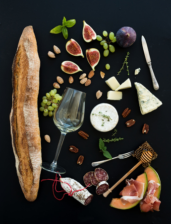 Wine and snack set. Baguette, glass of white, figs, grapes, nuts, cheese variety, meat appetizers and herbs on black grunge background, top view