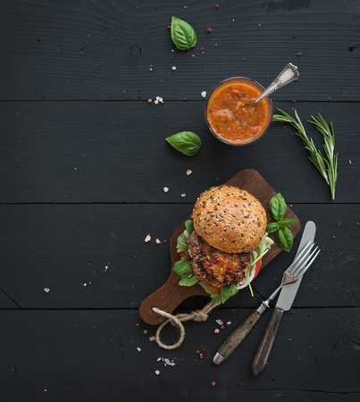 Fresh homemade burger on dark serving board with spicy tomato sauce, sea salt and herbs over dark wooden background. Top view, copy space