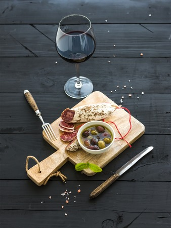 Wine appetizer set. Glass of red wine, French sausage and olives on black wooden backdrop, selective focus Standard-Bild