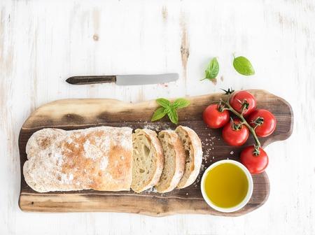 aceite de oliva: Pan chapata recién horneado con cereza-tomates, aceite de oliva, albahaca y sal en tablero de madera de nogal sobre fondo blanco, vista desde arriba, copia espacio
