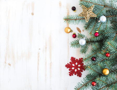 adornos navideños: Navidad o Año Nuevo decoración de fondo: las ramas de árbol de pieles, bolas de cristal de colores y brillantes estrellas sobre fondo de madera blanco, vista desde arriba, copia espacio