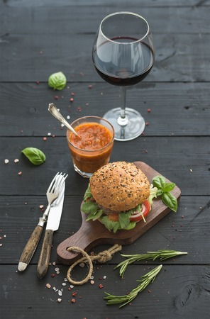 classic burger: Fresh homemade burger on dark serving board with spicy tomato sauce, sea salt, herbs and glass of red wine over black wooden background. Selective focus