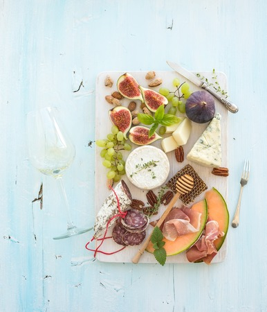 Wine and snack set. Figs, grapes, nuts, cheese variety, meat appetizers, herbs, glass on light blue background, top view Stock Photo