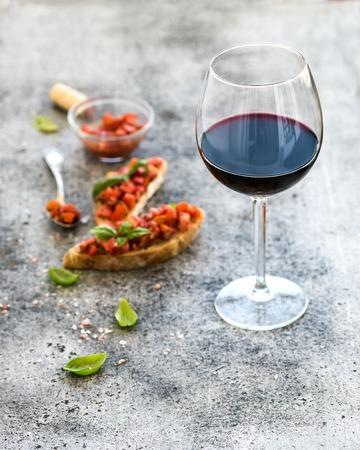 pan y vino: Wine appetizer set. Glass of red wine, brushettas with fresh tomato and basil on over rustic grunge grey backdrop
